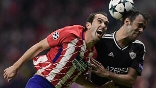 Diego Godin (left) said he was flattered by Manchester United's interest in his defensive services but preferred to stay in Madrid.