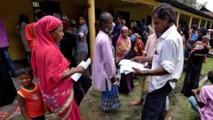 Người dân xếp hàng đợi kiểm tra giấy tờ bên ngoài trung tâm đăng ký công dân quốc gia (NRC) tại làng Mayong, bang Assam, Ấn Độ ngày 08/07/2018.