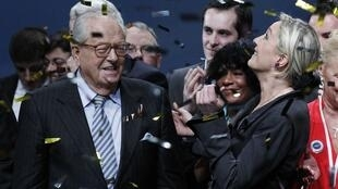 Jean-Marie Le Pen (L) hands over to daughter Marine at the Front National's congress in Tours