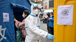 Un hombre con traje de protección controla el ingreso a un mercado en Wuhan, China