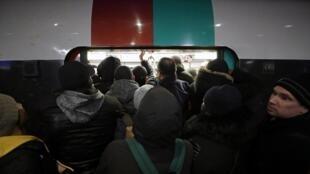 Les passagers montent à bord d'un métro à Gare du Nord lors de la grève de la RATP et de la SNCF à Paris, le 10 décembre 2019.
