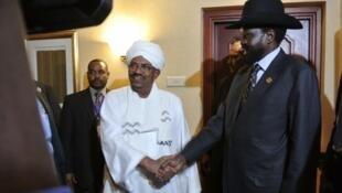 Sudanese President Omar al-Bashir (Center L) shakes hands with his South Sudanese counterpart Salva Kiir (Center R)