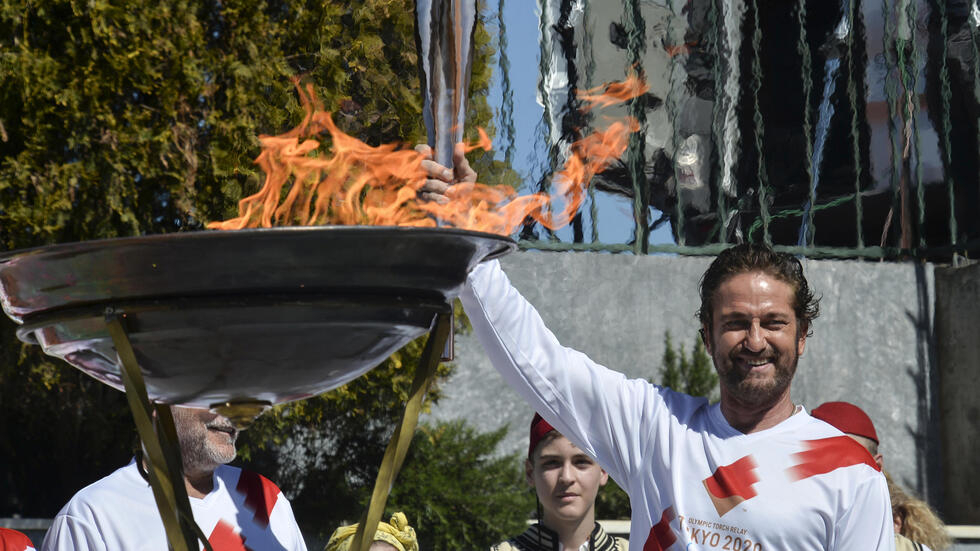 US actor Gerard Butler poses with the Olympic flame during the torch relay whoch was scrapped by Greek authorities alarmed by the large crowds