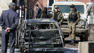Russian Interior Ministry servicemen stand next to a car that was blown up during a bombing in Karabulak