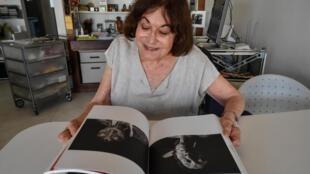 La photographe brésilienne d'origine suisse Claudia Andujar regarde des photos sur un livre lors d'une interview avec l'AFP à Sao Paulo, Brésil, le 29 octobre 2019.