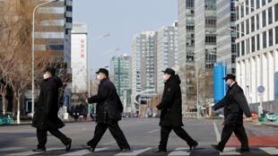 Des membres du personnel de sécurité portant des masques traversent une rue de Financial Street dans le centre de Pékin, le 3 février 2020.