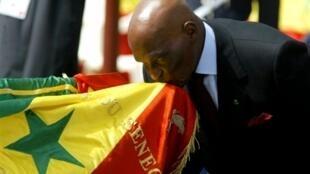 Le président Abdoulaye Wade embrasse le drapeau sénégalais le 4 avril 2006, à Dakar, lors du 46ème anniversaire de l'indépendance nationale.