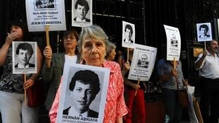 In this file photo taken in April, 2014, Beatriz Cantarini de Abriata, mother of missing architecture student Hernan Abriata, holds a portrait of her son while others hold portraits of former police officer Mario Sandoval.