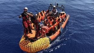 An inflatable dinghy belonging to the Ocean Viking rescue ship transports migrants rescued in the Mediterranean Sea on 12 August.