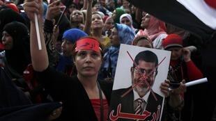 """An anti-Morsi protester carries a crossed-out picture of President Mohamed Morsi with the word """"leave"""", while chanting anti-Morsi and anti-Muslim Brotherhood slogans in Tahrir square in Cairo, 28 June 2013"""