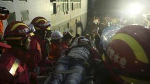 Equipes de resgate retiram em maca sobrevivente de deslizamento