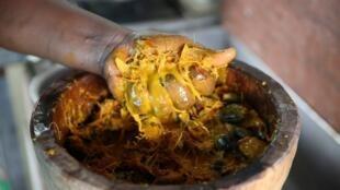 Une femme prépare le «nyembwe au poulet» -plat traditionnel gabonais- dans un restaurant à Libreville, le 25 mars 2018. (Photo d'illustration)