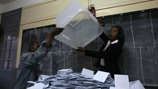 Electoral officials empty a ballot box before counting the cast votes at a polling centre in the capital Antananarivo
