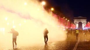Cảnh sát dùng vòi rồng để đẩy lùi những người Áo Vàng biểu tình trên đại lộ Champs - Elysées, Paris, Pháp, ngày 22/12/2018.