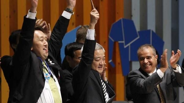 Japan's Environment Minister Ryu Matsumoto (C) holds the gavel, as Convention on Biological Diversity (CBD) Executive Secretary Ahmed Djoghlaf (R) claps