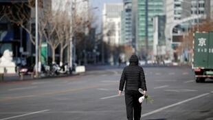 FILE PHOTO: A man walks along the Financial Street in central Beijing, China, as the country is hit by an outbreak of the new coronavirus, February 3, 2020.