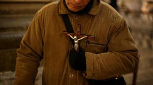 Un hombre sostiene un crucifijo en la catedral de Santiago de Chile, el 18 de mayo de 2018.