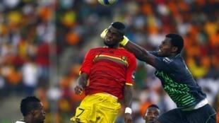 Ghana's goalkeeper Braimah Razak (R) saves the ball against Abdoul Camara (L) of Guinea