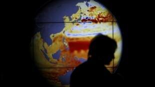 Una mujer pasa frente a un mapa que muestra el aumento del nivel de los mares en los últimos 22 años.