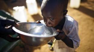 Un enfant buvant de l'eau dans le camp de réfugiés de Abu Shouk, à El-Fasher (Darfour), en mars 2013.