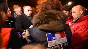French Interior Minister Gerard Collomb (L) meets with DDCS personnel on February 2, 2018 in Calais, northern France, following a large brawl between a hundred migrants which resulted in several injuries. Five migrants were in critical condition.