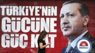 Una mujer pasa delante de un afiche del primer ministro turco y candidato a la presidencial Tayyip Erdogan, Estambul, 8 de agosto de 2014.