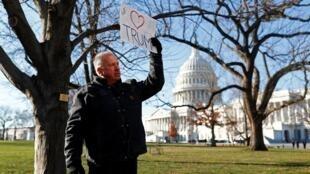 Un homme tient une pancarte en soutien au président américain Donald Trump avant le vote de destitution sur Capitol Hill à Washington le 18 décembre 2019.