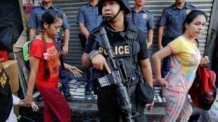 Un policier lors d'un raid anti-drogue à Quezon City, près de Manille, aux Philippines, le 12 octobre 2016.