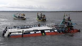 People climb onto the boat which sank on 19 December in east Java