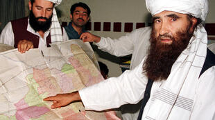 Jalaluddin Haqqani (R), the Taliban's Minister for Tribal Affairs, points to a map of Afghanistan during a visit to Islamabad, Pakistan, October 19, 2001, as his son Naziruddin (L) looks on.