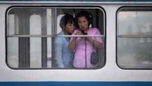 Deux femmes regardant sur un smartphone dans le tramway de Pyongyang.