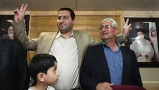 Alleged nuclear scientist Shahram Amiri with his father and son at Tehran airport, 15 July 2010.