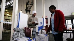 Une femme dépose son bulletin dans l'urne dans un township du Cap le 8 mai 2019.