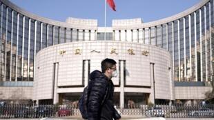 Homem de máscara caminha em rua praticamente deserta em frente ao Banco Central da China, em Pequim.