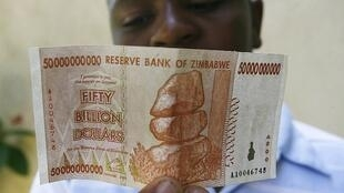 A Zimbabwean looks at a new 50 billion Zimbabwean dollar bank note issued in January 2009.