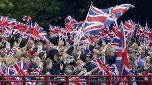 Gente hace ondear banderas británicas mientras la reina Isabel II embarca en el navío real, este 3 de junio de 2012.