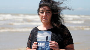 """Beatrice Huret poses with her book titled """"Calais Mon Amour"""" .Her book she recounts the story of her romance with her lover Mokhtar, an Iranian migrant she had met in the so-called Jungle migrant camp in Calais. Picture taken June 15, 2017."""