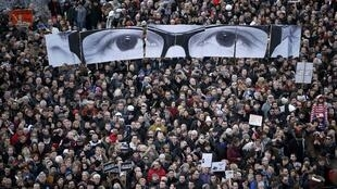 """People hold panels to create the eyes of late Charlie Hebdo editor  """"Charb"""" at the solidarity march in Paris, 11 January 2015."""