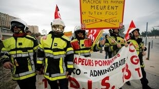 Firefighters hold a sign as French Labour unions members demonstrate against French government's pensions reform plans in Marseille as part of a day of national strike and protests in France, December 5, 2019.