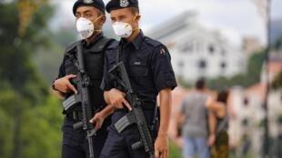 Des policiers malaisiens patrouillent dans Kuala Lampur en portant des masques de protection, le 10 février 2020.