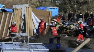 Workmen tear down shacks at the Jungle on Monday