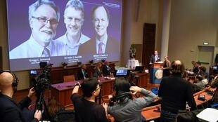 Os laureados do Prêmio Nobel de Medicina deste ano: William G. Kaelin Jr., Sir Peter J. Ratcliffe e Gregg L. Semenza aparecem no telão da Academia, em Estocolmo, na Suécia.