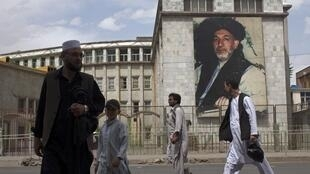 Afghans walk past a picture of Afghan President Hamid Karzai on a street in Kabul
