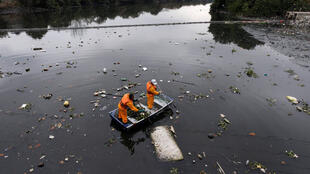 Garbage collectors hired by the Brazilian government pluck out rubbish from Guanabara bay on 20 July 2016.