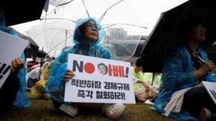 """Dòng chữ trên biểu ngữ của người phụ nữ Hàn Quốc trong cuộc biểu tình chống Nhật ở Seoul ngày 15/08/2019: """"Không, ông Abe, hãy rút lại trừng phạt!""""."""