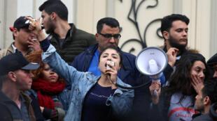 Des manifestants scandent des slogans au mégaphone lors d'un rassemblement à Tunis le 9 janvier 2018.