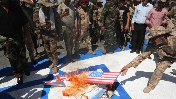 In this file photo taken on May 31, 2019 Iraqi Shiite fighters from the Iran-backed armed group, Hezbollah brigades, burn a US a