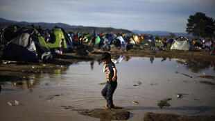 A boy carries a bottle of water as he walks through mud waiting to cross the Greek-Macedonian border, at a makeshift camp for migrants near the village of Idomeni, Greece March 8, 2016.