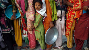 Flood victims queue for food handouts in Sindh province.