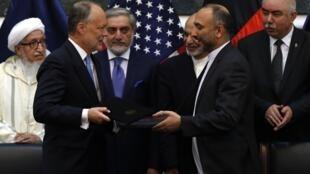 Ханиф Атмар, советник по национальной безопасности Афганистана и посол США Джеймс Каннингам после подписания договора по безопасности в Кабуле 30/09/2014
